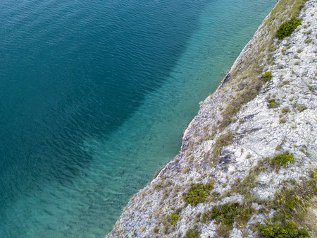 Aerial view of rocks on the sea. Seen from above, transparent water. Cliff