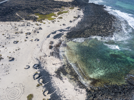 Aerial view of the Caleta del Mojón Blanco, sandy desert beach and rugged coastline. Orzola, Lanzarote, Canary Islands, Spain, Africa