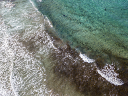 Aerial view of a crystal clear sea with waves and surfers. Playa De La Canteria. Atlantic Ocean, waves crashing on the beach at sunset, backlighting. Orzola, Lanzarote, Canary Islands. spain Reklamní fotografie