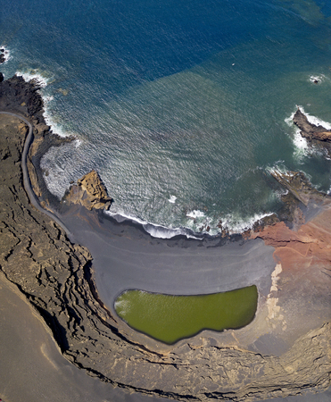 Aerial view of the Charco de los Clicos, a small salt-water lake with an emerald green color set in a black pebble beach, view of the rock formations bordering the lake. Lanzarote, Canary Islands, Spain, Europe 免版税图像