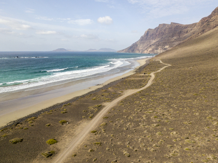 Aerial view of Famara beach, Lanzarote, Canary Islands, Spain. Rising of Famara, relief, mountains overlooking the Atlantic Ocean. Unpaved road that runs along the coast