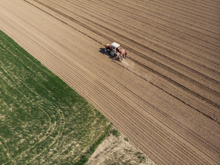 Aerial view of a tractor plowing the fields, aerial view, plowing, sowing, harvest. Agriculture and Farming, campaign. Desert and dehydrated lands, global warming