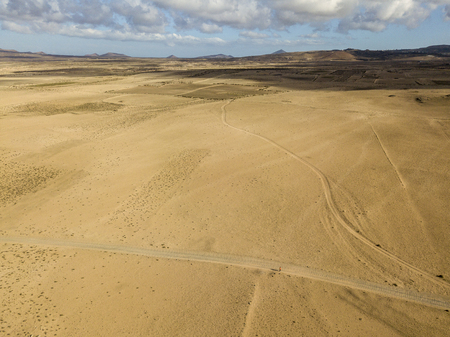 Aerial view of a desert landscape on the island of Lanzarote, Canary Islands, Spain. Road that crosses a desert. A man with an orange t-shirt walking in a desert land