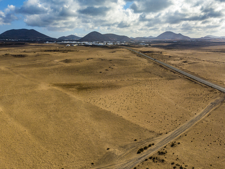 Aerial view of a desert landscape on the island of Lanzarote, Canary Islands, Spain. Road that crosses a desert. Tongue of black asphalt. Reliefs on the horizon. Volcanoes.