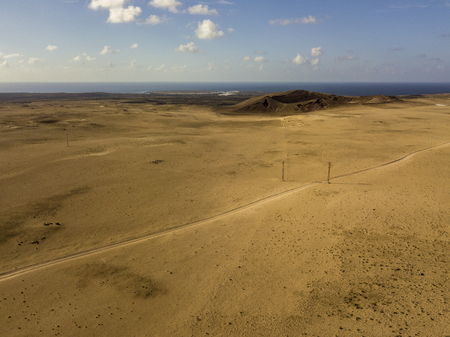 Aerial view of a desert landscape on the island of Lanzarote, Canary Islands, Spain. Road that crosses a desert. Reliefs on the horizon. Volcanoes. Reklamní fotografie