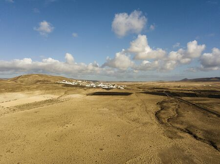 Aerial view of a desert landscape on the island of Lanzarote, Canary Islands, Spain. Mountains of the village of Soo and in the background Famara. Reliefs and volcanoes on the horizon