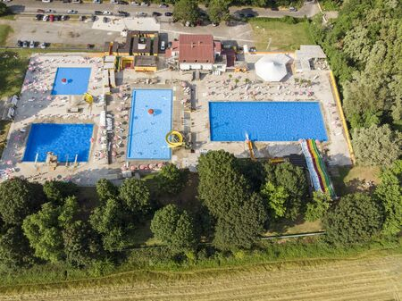 Aerial view of swimming pools. Summer and holiday periods, crystal clear water. Trampolines, slides and water games. Complex of pools, umbrellas and deck chairs. Green area. Il Gabbiano in Limbiate, Milan, Italy