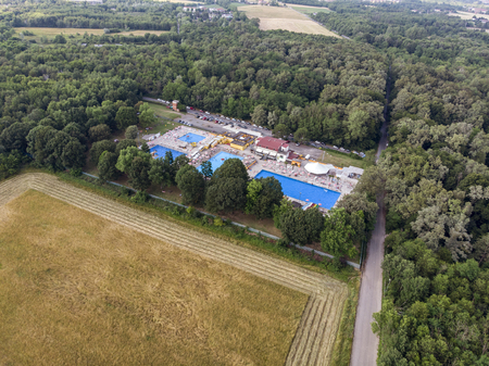 Aerial view of swimming pools. Summer and holiday periods, crystal clear water. Trampolines, slides and water games. Complex of pools, umbrellas and deck chairs. Green area. Editorial