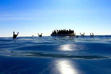 Refugees on a rubber boat in the middle of the sea that require help. Sea with people asking for help. Migrants crossing the sea 免版税图像