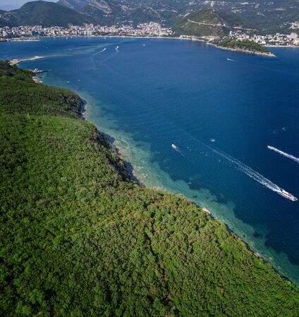 Aerial view of boats and watercraft, jagged and lush coasts. Mediterranean scrub. Sea, crystal clear water. Sveti Nikola, Budva island, Montenegro
