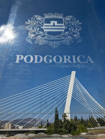 Podgorica, emblem of the capital printed on a transparent panel on the Moscow Bridge. In the background the Millenium bridge. 09/15/2019. Modern architecture of the capital of Montenegro