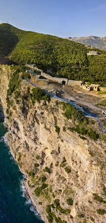 Aerial view of Mogren Fortress, Tvrdava Mogren, it is located on a promontory Mogren between the beaches Mogren and Jaz just a kilometer from the town of Budva. Montenegro. Jagged coast