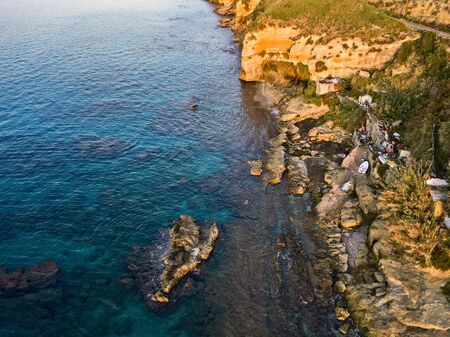 Aerial view of fishermen on the rocks, shacks and fishing posts on a cliff by the sea. Disused houses, huts, shelters and slums. Italian coast, Pizzo Calabro, Calabria. italy