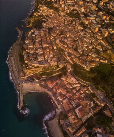 Aerial view of Pizzo Calabro, pier, castle, Calabria, tourism Italy. Pizzo Calabro by the sea. Houses on the rock. On the cliff stands the Aragonese castle. Seafront at sunset