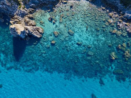 Aerial view of Tropea beach, crystal clear water and rocks that appear on the beach. Calabria, Italy. Swimmers, bathers floating on the water. Tyrrhenian Sea. Coastline of Calabria Фото со стока