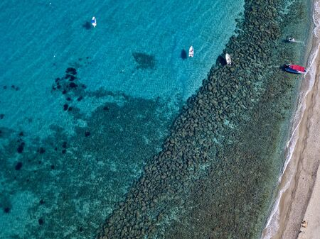 Aerial view of boats at the Tropea beach, deck chairs and umbrellas by the sea. Crystal and clear water. Calabria, Italy