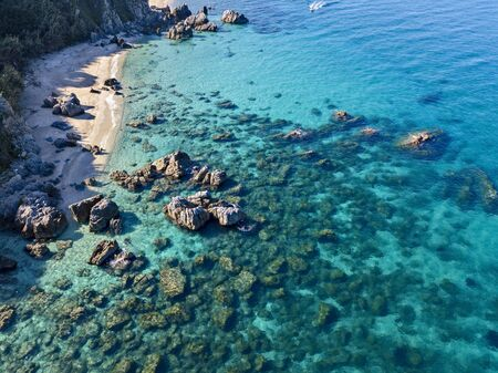 Aerial view of Tropea beach, crystal clear water and rocks that appear on the beach. Calabria, Italy. Swimmers, bathers floating on the water. Coastline of Calabria