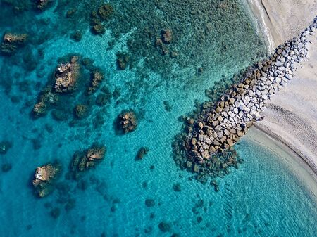 Aerial view of Tropea beach, crystal clear water and rocks that appear on the beach. Calabria, Italy. Swimmers, bathers floating on the water. Coastline of Calabria Фото со стока