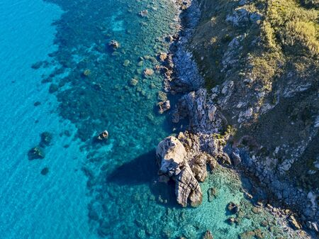 Aerial view of Tropea beach, crystal clear water and rocks that appear on the beach. Rock Pizzuta. Calabria, Italy