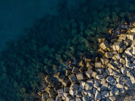 Aerial view of rocks on the sea. Overview of seabed seen from above, transparent water. Фото со стока