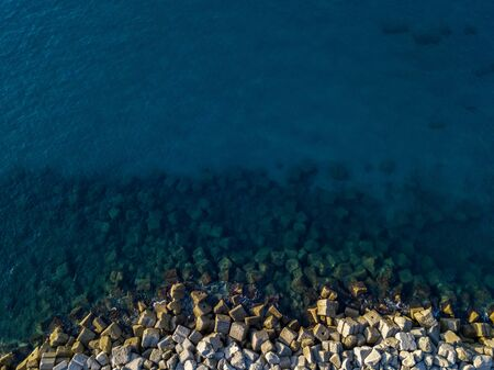 Aerial view of rocks on the sea. Overview of seabed seen from above, transparent water.