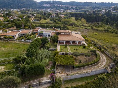Aerial view of the Calabrian coast, villas and resorts on the cliff. Transparent sea and wild coast. Locality of Riaci near Tropea, Calabria. Italy