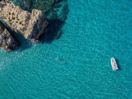 Aerial view of the Riaci rocks, Riaci beach near Tropea, Calabria. Italy. Beaches and crystal clear sea. A dinghy moored and swimmers who swim and snorkel Фото со стока