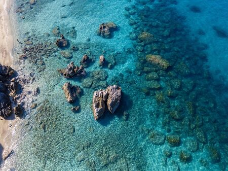 Aerial view of Tropea beach, crystal clear water and rocks that appear on the beach. Calabria, Italy. Swimmers, bathers floating on the water. Tyrrhenian Sea. Coastline of Calabria