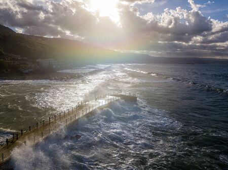 Aerial view of a pier with rocks and rocks on the sea. Pizzo Calabro pier, panoramic view from above. Broken pier, force of the sea. Power of Waves. Natural disasters, climate change. Calabria, Italy