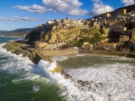 Aerial view of Pizzo Calabro, broken pier, castle, Calabria, tourism Italy. Houses on the rock. On the cliff stands the Murat Aragonese castle. Seafront at sunset. Sea storm and waves with wind