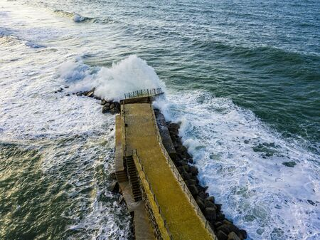 Aerial view of a pier with rocks and rocks on the sea. Pizzo Calabro pier, panoramic view from above. Broken pier, force of the sea. Power of Waves. Natural disasters, climate change. Calabria, Italy.