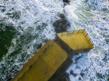 Aerial view of a pier with rocks. Pizzo Calabro pier, panoramic view from above. Broken pier, force of the sea. Power of Waves. Natural disasters, climate change. Calabria, Italy.