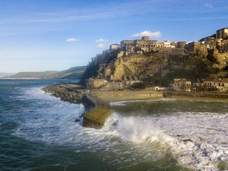 Aerial view of Pizzo Calabro, broken pier, castle, Calabria, tourism Italy. Houses on the rock. On the cliff stands the Murat Aragonese castle. Seafront at sunset. Sea storm and waves with wind Фото со стока