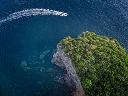 Aerial view of a steep cliff and a motor boat. Jagged coast on the Adriatic Sea. Cliffs overlooking the transparent sea. Wild nature and Mediterranean maquis