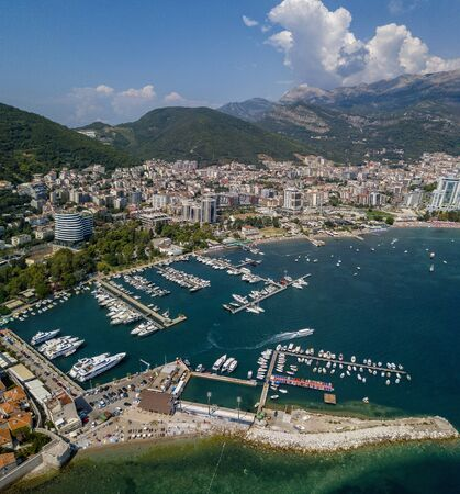 Aerial view of boats moored at the Budva Harbor, Montenegro. Modern Budva on the background. Beaches and transparent sea. Vacation and tourism