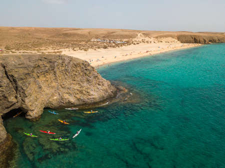 Aerial view of the jagged shores and beaches of Lanzarote, Spain, Canary. Roads and dirt paths. Walking routes to explore the island. Bathers on the beach. Atlantic Ocean. Papagayo