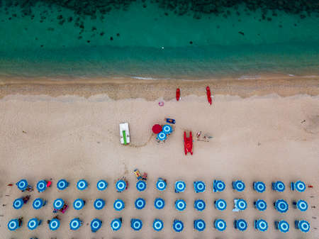 Aerial view of a beach and umbrellas. Tropea, Calabria, Italy. Parghelia. Overview of seabed seen from above, transparent water. Swimmers, bathers floating on the water. Lido La Grazia