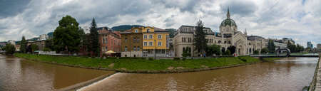 Panoramic view of the river Miljacka, The Academy of Fine Arts is the building in the background and the Festina Lente bridge on the right side. Sarajevo. Bosnia and Herzegovina. 07-08-2018