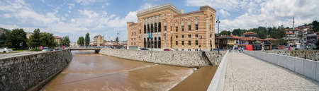 Panoramic view of the Sarajevo City Hall, Vijećnica. It was the National and University Library of Bosnia and Herzegovina. 07-08-2018. River Miljacka. Houses, mountains, hills and roofs of the city Stok Fotoğraf