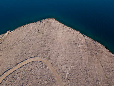 Aerial view of Rucica beach on Pag island, Metajna, Croatia. Seabed and beach seen from above, bathers, relaxation and summer holidays. Promontories and cliffs of Croatian coasts