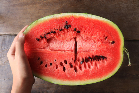 Cut in half watermelon on wooden table background Stock Photo