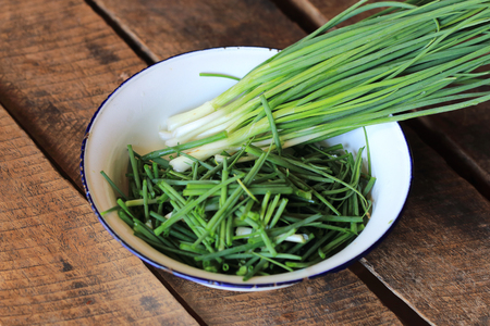 Chopped scallion or spring onion leaves in a white bowl on wood background
