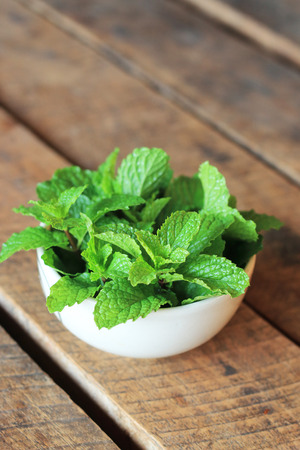 Fresh mint in bowl on wooden table background