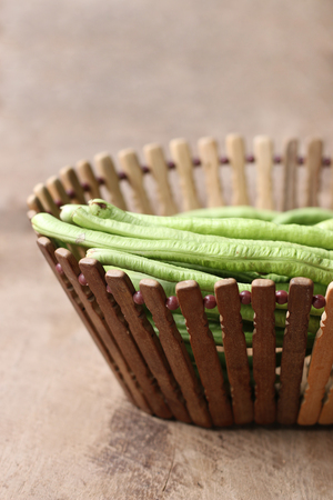 long bean: yard long bean in basket on wooden table background Stock Photo