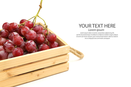 Red grape in a wooden crate on white background. Stock Photo