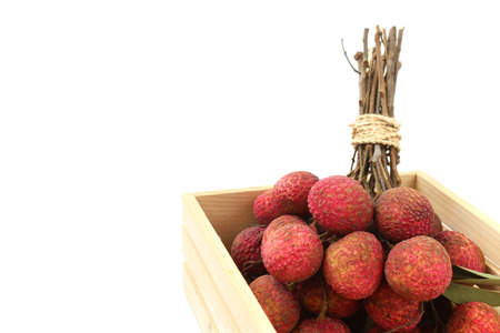 lychee in a wooden crate on white background.