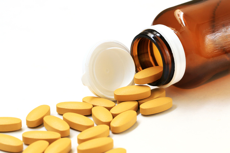 Pills of vitamin C spilled out open bottle on white background.
