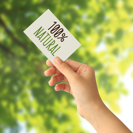 Hand holding a paper card with One hundred percent natural word on abstract nature background