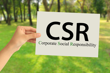 Hand holding a paper card with Corporate social responsibility (CSR) concept on abstract nature background