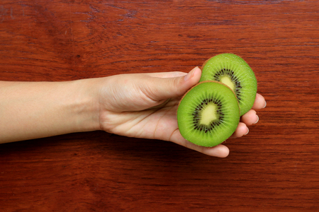 Hand holding half kiwi fruits on wooden table background